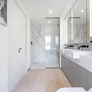 Ispirazione per una stanza da bagno con doccia minimal con ante lisce, ante grigie, doccia alcova, WC sospeso, piastrelle grigie, piastrelle bianche, lastra di pietra, pareti bianche, parquet chiaro, lavabo da incasso, pavimento beige, doccia aperta e top bianco