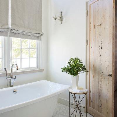 Beach style beige floor freestanding bathtub photo in Other with white walls