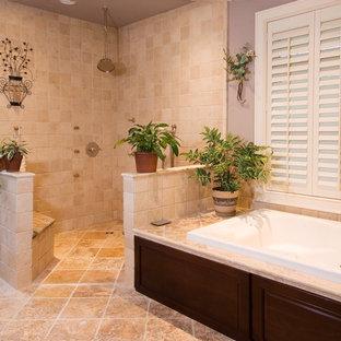 Ispirazione per una grande stanza da bagno padronale chic con lavabo sottopiano, ante con bugna sagomata, ante in legno bruno, top in granito, vasca da incasso, doccia aperta, WC monopezzo, piastrelle beige, piastrelle in pietra, pareti viola e pavimento in marmo