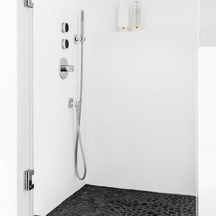 Foto di una stanza da bagno padronale design di medie dimensioni con doccia alcova, piastrelle nere, piastrelle di ciottoli, pareti bianche e pavimento in cemento