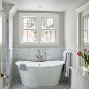 Modelo de cuarto de baño clásico con armarios con rebordes decorativos, puertas de armario blancas, bañera exenta, baldosas y/o azulejos grises, baldosas y/o azulejos de mármol, paredes grises, suelo con mosaicos de baldosas, suelo gris y encimeras blancas