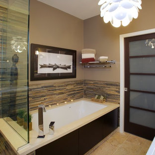 Photo of a large asian master bathroom in Chicago with flat-panel cabinets, dark wood cabinets, multi-coloured tile, an undermount tub, a corner shower, a one-piece toilet, matchstick tile, beige walls, travertine floors, a vessel sink and solid surface benchtops.