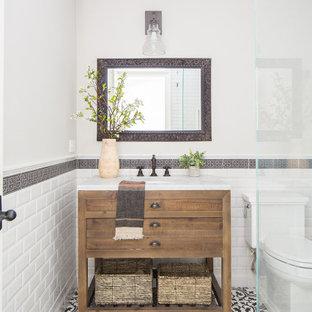 Lantlig inredning av ett litet vit vitt badrum med dusch, med möbel-liknande, skåp i mellenmörkt trä, en hörndusch, en toalettstol med hel cisternkåpa, svart och vit kakel, keramikplattor, beige väggar, cementgolv, ett undermonterad handfat, marmorbänkskiva, flerfärgat golv och dusch med gångjärnsdörr