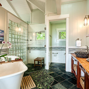 Idee per una stanza da bagno padronale tropicale di medie dimensioni con consolle stile comò, ante in legno scuro, vasca freestanding, doccia ad angolo, bidè, piastrelle verdi, piastrelle di vetro, pareti verdi, pavimento con piastrelle a mosaico, lavabo a colonna e top in legno