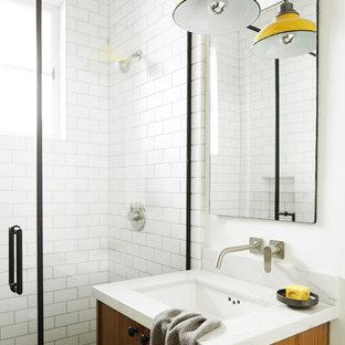 Lantlig inredning av ett litet vit vitt badrum med dusch, med släta luckor, skåp i mellenmörkt trä, en dusch i en alkov, vit kakel, keramikplattor, vita väggar, klinkergolv i småsten, ett undermonterad handfat, bänkskiva i kvartsit, grått golv och dusch med gångjärnsdörr