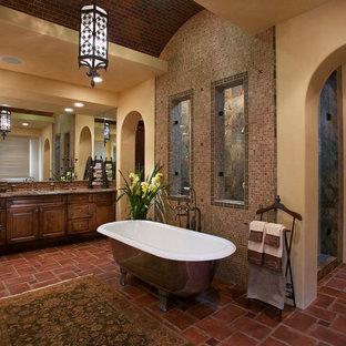 Diseño de cuarto de baño mediterráneo con bañera exenta, baldosas y/o azulejos en mosaico y suelo de baldosas de terracota