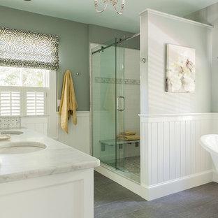 Modelo de cuarto de baño principal, clásico, de tamaño medio, con puertas de armario blancas, bañera con patas, suelo de baldosas de porcelana, suelo gris, encimeras grises, ducha empotrada, paredes grises, lavabo bajoencimera y ducha con puerta corredera