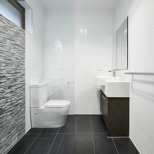 Esempio di una stanza da bagno minimalista con lavabo a bacinella, ante lisce, ante in legno bruno, piastrelle grigie, piastrelle a listelli, pareti bianche e pavimento nero