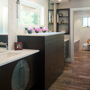 Example of a trendy pebble tile bathroom design in Austin with an undermount sink and black cabinets