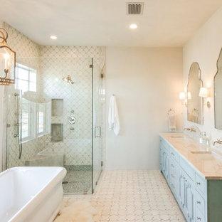 オースティンの大きいカントリー風おしゃれな浴室 (青いキャビネット、置き型浴槽、段差なし、ベージュのタイル、テラコッタタイル、ベージュの壁、テラコッタタイルの床、アンダーカウンター洗面器、珪岩の洗面台、開き戸のシャワー、ベージュのカウンター) の写真