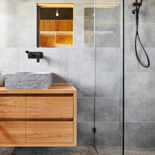 Inspiration for a contemporary master bathroom in Geelong with medium wood cabinets, wood benchtops, flat-panel cabinets, an alcove shower, gray tile, a vessel sink, grey floor and a floating vanity.