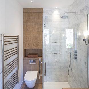 Exemple d'une petite salle d'eau tendance avec un placard à porte plane, des portes de placard en bois brun, un WC suspendu, un mur blanc, une douche d'angle, un carrelage marron et un carrelage blanc.