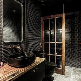 Foto di una grande stanza da bagno industriale con doccia ad angolo, WC monopezzo, piastrelle nere, piastrelle in ceramica, pareti nere, pavimento con piastrelle in ceramica, top in marmo, pavimento grigio e doccia aperta