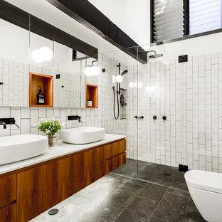 Imagen de cuarto de baño con ducha, urbano, con armarios con paneles lisos, puertas de armario de madera oscura, ducha empotrada, sanitario de pared, paredes blancas, lavabo sobreencimera, suelo gris y ducha con puerta con bisagras