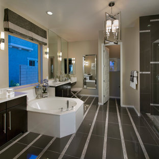 Drop-in bathtub - transitional black tile drop-in bathtub idea in Phoenix with an integrated sink, flat-panel cabinets and dark wood cabinets