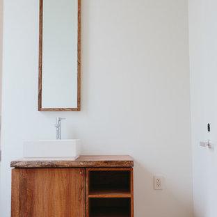 Ejemplo de cuarto de baño principal, moderno, de tamaño medio, con lavabo sobreencimera, armarios abiertos, puertas de armario de madera oscura, encimera de madera, paredes blancas y encimeras marrones