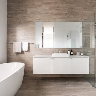 Contemporary master bathroom in Perth with flat-panel cabinets, white cabinets, a freestanding tub, a curbless shower, gray tile, a vessel sink, grey floor and white benchtops.