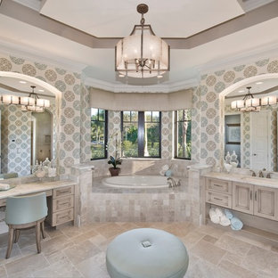 Example of a large tuscan master travertine floor and beige floor bathroom design in Miami with an undermount sink, recessed-panel cabinets, multicolored walls, beige cabinets and marble countertops
