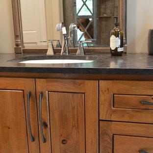 ミルウォーキーの大きいラスティックスタイルのおしゃれなマスターバスルーム (中間色木目調キャビネット、ベージュの壁、アンダーカウンター洗面器、ソープストーンの洗面台、レイズドパネル扉のキャビネット、黒い洗面カウンター) の写真