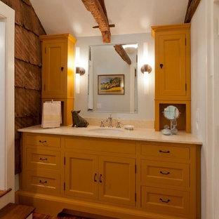 Klassisk inredning av ett stort badrum med dusch, med skåp i shakerstil, gula skåp, vita väggar, mellanmörkt trägolv, ett nedsänkt handfat och bänkskiva i akrylsten