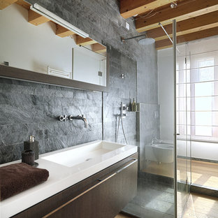 Inspiration for a contemporary bathroom in London with flat-panel cabinets, dark wood cabinets, an alcove shower, a bidet, grey walls, light hardwood floors, an integrated sink and slate.