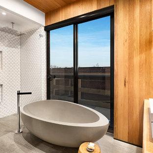 Imagen de cuarto de baño principal, moderno, de tamaño medio, con lavabo sobreencimera, armarios con paneles lisos, puertas de armario de madera clara, encimera de madera, bañera exenta, ducha abierta, baldosas y/o azulejos blancos, baldosas y/o azulejos de cerámica y suelo de pizarra
