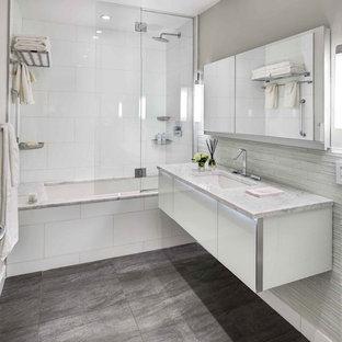 Стильный дизайн: большая главная ванная комната в стиле модернизм с плоскими фасадами, белыми фасадами, душем над ванной, плиткой из листового камня, накладной раковиной, ванной в нише, коричневыми стенами, полом из керамогранита, серым полом и душем с распашными дверями - последний тренд