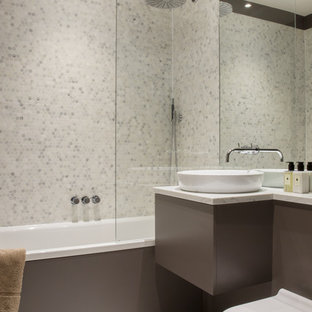 Small contemporary bathroom in London with a built-in bath, a shower/bath combination, a bidet, grey tiles, white tiles, marble tiles, a wall-mounted sink and white floors.
