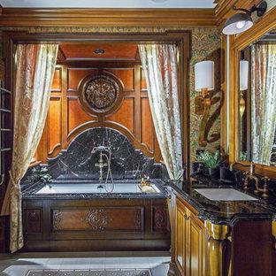 Идея дизайна: ванная комната в классическом стиле с фасадами цвета дерева среднего тона, полновстраиваемой ванной, душем над ванной, мраморной плиткой, коричневыми стенами, врезной раковиной, мраморной столешницей, белым полом, шторкой для ванной, черной столешницей и фасадами с выступающей филенкой