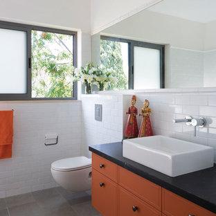 Diseño de cuarto de baño moderno con lavabo sobreencimera, puertas de armario naranjas y paredes blancas