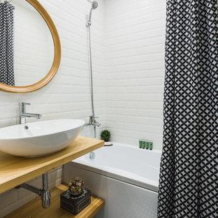Создайте стильный интерьер: ванная комната в скандинавском стиле с душем над ванной, керамической плиткой, полом из керамической плитки, открытыми фасадами, ванной в нише, белой плиткой, настольной раковиной, столешницей из дерева, светлыми деревянными фасадами, шторкой для душа и бежевой столешницей - последний тренд