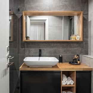 Bild på ett litet minimalistiskt brun brunt badrum med dusch, med laminatgolv, släta luckor, svarta skåp, grå kakel, grå väggar, ett fristående handfat, träbänkskiva och grått golv