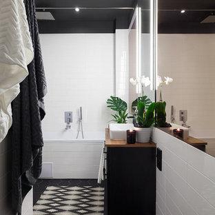 Ejemplo de cuarto de baño principal, de estilo americano, pequeño, con armarios tipo mueble, puertas de armario negras, bañera encastrada sin remate, combinación de ducha y bañera, sanitario de pared, baldosas y/o azulejos blancas y negros, baldosas y/o azulejos de porcelana, paredes grises, suelo de baldosas de porcelana, lavabo tipo consola y encimera de laminado