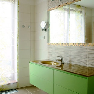 This is an example of a large modern family bathroom in Other with flat-panel cabinets, green cabinets, a built-in bath, a built-in shower, a bidet, beige tiles, ceramic tiles, beige walls, ceramic flooring, an integrated sink and glass worktops.