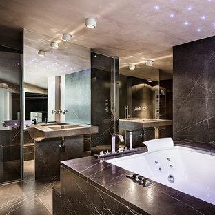 Imagen de cuarto de baño principal, contemporáneo, grande, con jacuzzi, baldosas y/o azulejos negros, losas de piedra, paredes negras, suelo de mármol y lavabo integrado