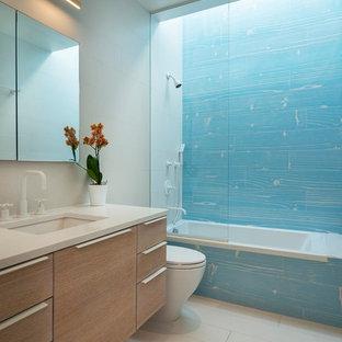 Пример оригинального дизайна: ванная комната в современном стиле с плоскими фасадами, светлыми деревянными фасадами, накладной ванной, душем над ванной, синей плиткой, серыми стенами, врезной раковиной, серым полом и белой столешницей
