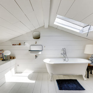 This is an example of a mid-sized traditional master bathroom in Paris with white walls, white floor, a claw-foot tub, painted wood floors, a wall-mount sink, white tile and white benchtops.