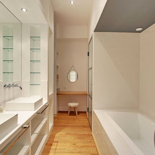 This is an example of a large contemporary ensuite bathroom in Other with open cabinets, a built-in bath, metro tiles, white walls, a vessel sink, white tiles and medium hardwood flooring.