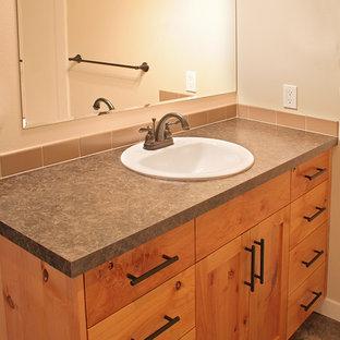 シアトルの中くらいのおしゃれな浴室 (オーバーカウンターシンク、シェーカースタイル扉のキャビネット、中間色木目調キャビネット、ラミネートカウンター、ベージュのタイル、セラミックタイル、ベージュの壁、リノリウムの床) の写真