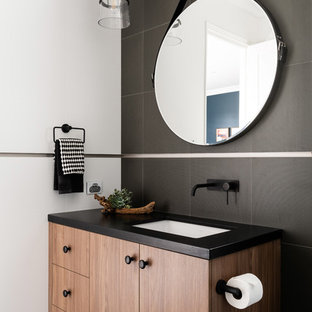 Photo of a contemporary bathroom in Perth with flat-panel cabinets, medium wood cabinets, black tile, black walls, an undermount sink, black floor and black benchtops.