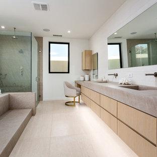 Diseño de cuarto de baño principal, actual, grande, con armarios con paneles lisos, puertas de armario de madera clara, bañera encastrada sin remate, ducha a ras de suelo, paredes blancas, lavabo integrado, encimera de cemento, suelo beige, ducha con puerta con bisagras y encimeras grises