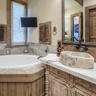 Idée de décoration pour une salle de bain chalet avec un placard en trompe-l'oeil, des portes de placard en bois vieilli, une baignoire posée, un carrelage gris, un mur beige, une vasque et un plan de toilette blanc.