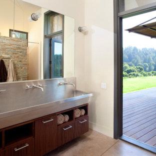 Ispirazione per una stanza da bagno moderna di medie dimensioni con lavabo rettangolare, ante in legno bruno, top in acciaio inossidabile, piastrelle grigie, piastrelle in pietra e pareti bianche