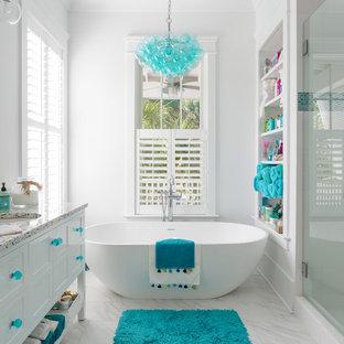 На фото: маленькая главная ванная комната в морском стиле с фасадами островного типа, белыми фасадами, отдельно стоящей ванной, белыми стенами, столешницей терраццо, разноцветной столешницей, врезной раковиной и белым полом с
