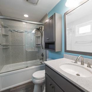 Ejemplo de cuarto de baño con ducha, contemporáneo, de tamaño medio, con armarios con rebordes decorativos, puertas de armario grises, bañera encastrada, ducha empotrada, paredes azules, suelo vinílico, lavabo integrado, encimera de ónix, suelo marrón y ducha con puerta corredera