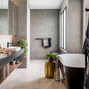 Immagine di una grande stanza da bagno padronale minimal con vasca freestanding, piastrelle grigie, pareti grigie, nessun'anta, doccia a filo pavimento, lavabo da incasso, pavimento grigio, doccia aperta e top grigio