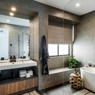 Contemporary master bathroom in Gold Coast - Tweed with flat-panel cabinets, medium wood cabinets, a freestanding tub, a curbless shower, gray tile, grey walls, a wall-mount sink and grey floor.