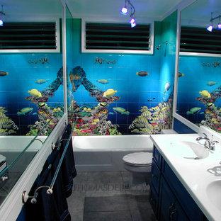 Modelo de cuarto de baño tropical con puertas de armario azules, bañera esquinera, sanitario de una pieza, baldosas y/o azulejos negros, baldosas y/o azulejos de cemento, paredes azules, lavabo encastrado, suelo negro y encimeras blancas