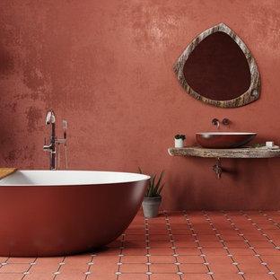 Modelo de cuarto de baño principal, mediterráneo, grande, con armarios abiertos, bañera exenta, paredes rojas, lavabo sobreencimera, encimera de madera y suelo rojo