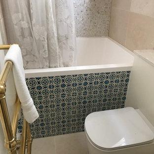 Idée de décoration pour une petite salle de bain méditerranéenne pour enfant avec un placard avec porte à panneau surélevé, des portes de placard beiges, un bain japonais, un combiné douche/baignoire, un WC suspendu, un carrelage beige, des carreaux de céramique, un mur beige, un sol en carrelage de céramique, un lavabo intégré, un plan de toilette en surface solide, un sol beige et une cabine de douche avec un rideau.
